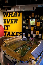 "Installation photo of ""Pittsburgh Electric Football Heinz Field,"" John and Shawna Evans and Rob Dalmasse, 2003 and display of unlicensed Steelers T-shirts, with slide show ""Great Moments in Unlicensed Steelers T-shirts,"" Images courtesy of Pittsburgh Sports and Mini Ponies blog, video slide show, 2010."