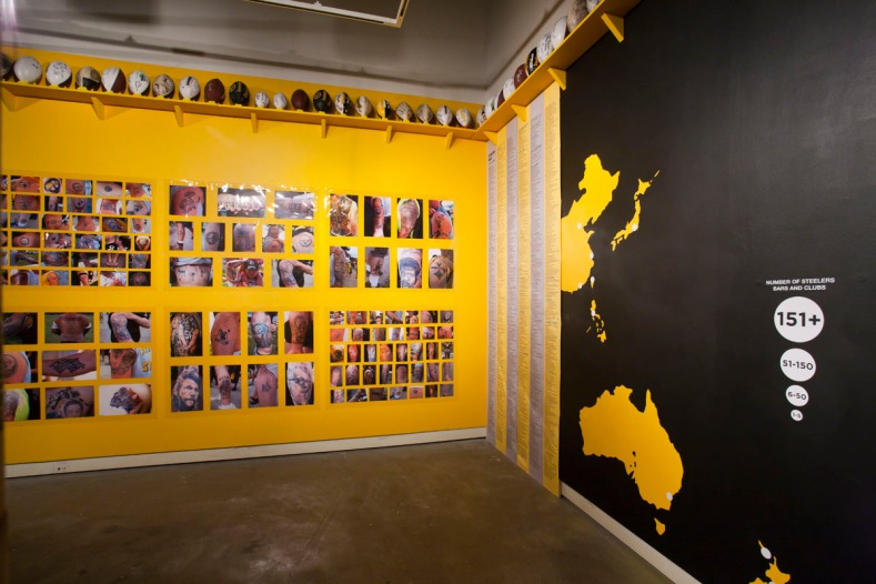 "Installation photograph of ""Whatever It Takes,"" with Tattoo Parlor, 102 Signed Footballs (collection of Shawn Spinda), and Steelers Nation Map"