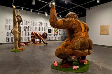 Installation shot: Foreground: Ladies Sasquatch (2006-2010); Found textiles, taxidermy supplies, appliqué borg, styrofoam, wood. Recommended Reading (2010); Wallpaper of photocopied drawings. Both by Allyson Mitchell and courtesy of the artist and Katharine Mulherin Gallery, Toronto.