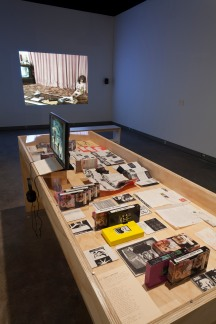 Installation shot: Foreground: Joanie 4 Jackie (1995-2003); VHS masters, tapes and DVDs from the Chainletter Series with accompanying booklets of letters written by each filmmaker to other women on their compilation, VHS tapes from the Co-Star Series with accompanying posters, personal correspondence from July's collection; Courtesy of the artists and Bard College, Annandale-on-Hudson. Background: Videos (1996-2001) by July; Single-channel video with sound, 57:30 minutes; Courtesy of the artist and Video Data Bank, Chicago.